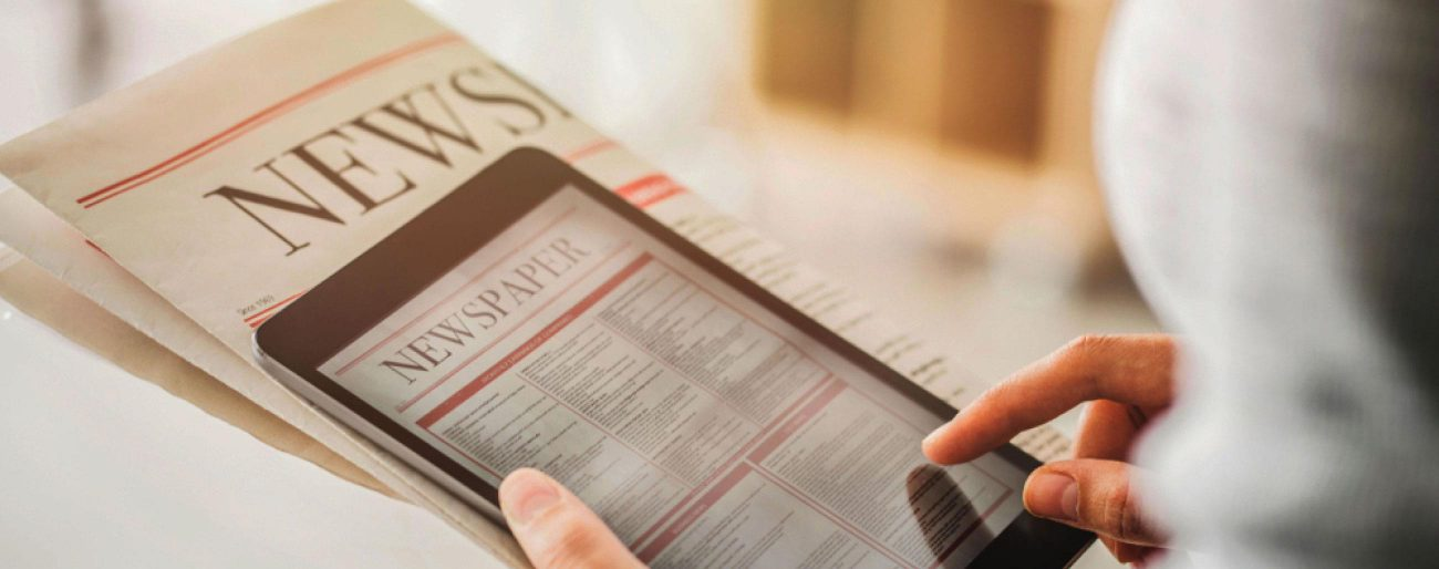 person holding folded newspaper and tablet