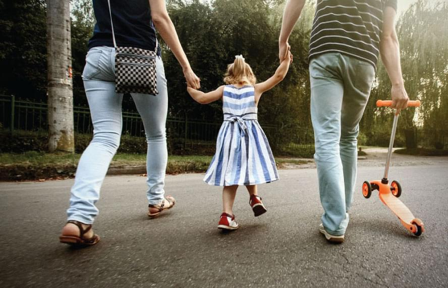little girl holding her parents' hands, walking on pavement