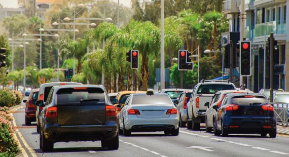 cars on city street stopped at traffic light