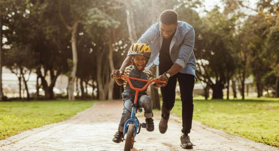man helping young child ride a bike