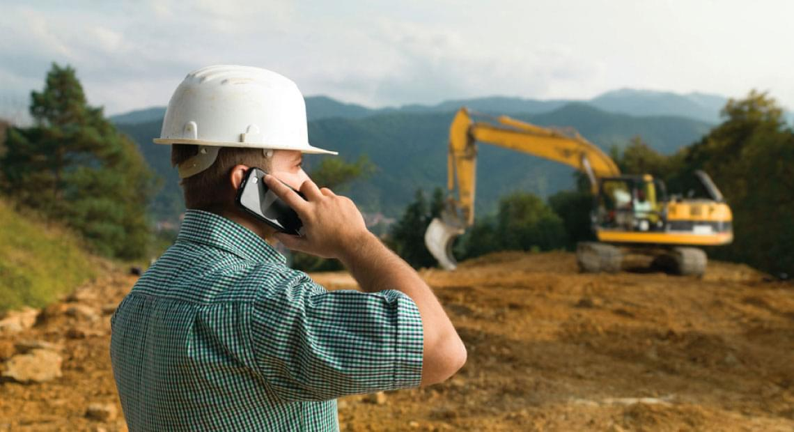 land management worker near construction site talking on cell phone